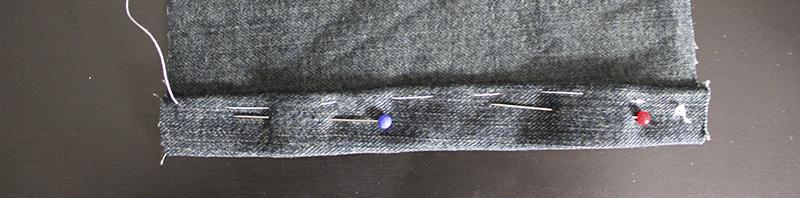 Hilvanar tela del bajo de un pantalón tejano