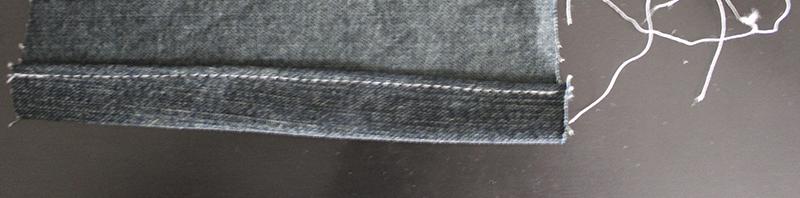 Cosido de la tela del bajo de un pantalón vaquero